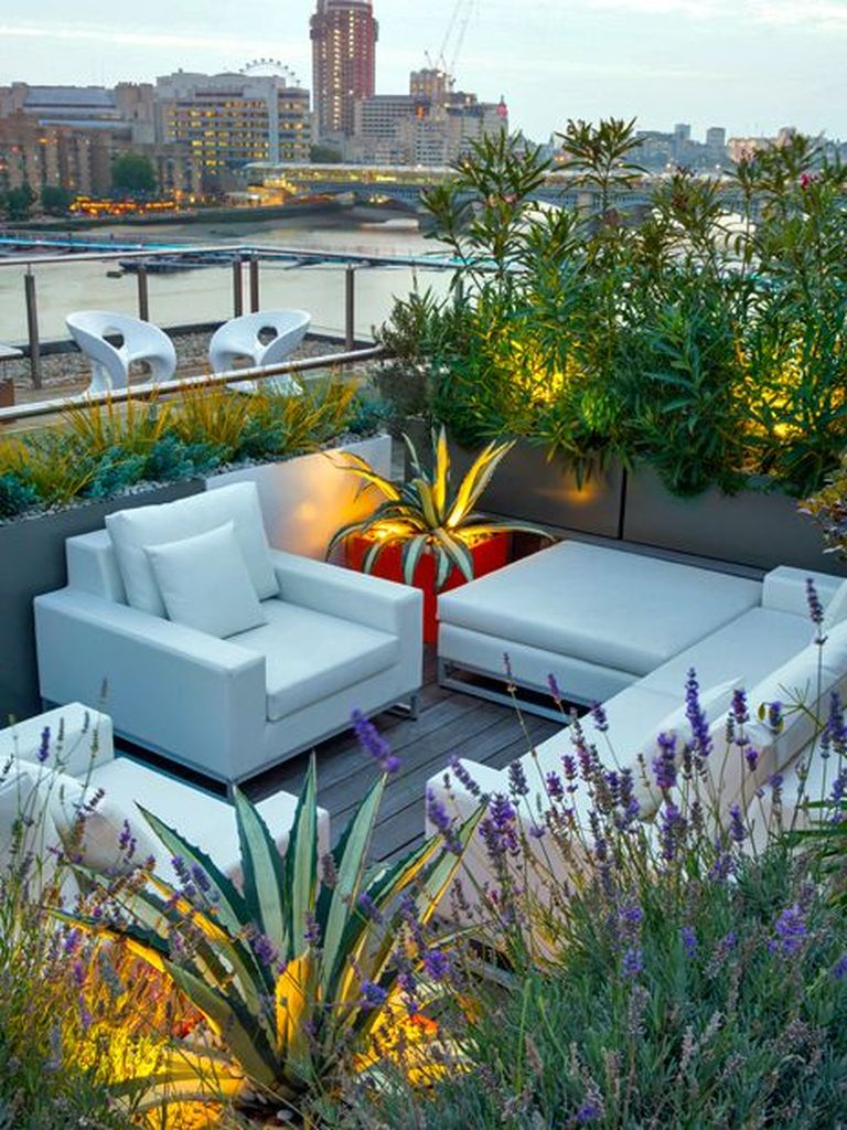An elegant small rooftop lighting combined with white sofa and lighting merge on the plant to beautify your rooftop garden