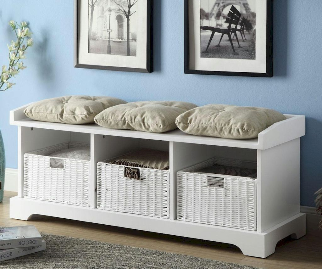 An elegant white wooden storage bench with basket below it and cushion to perfect your entryway decor