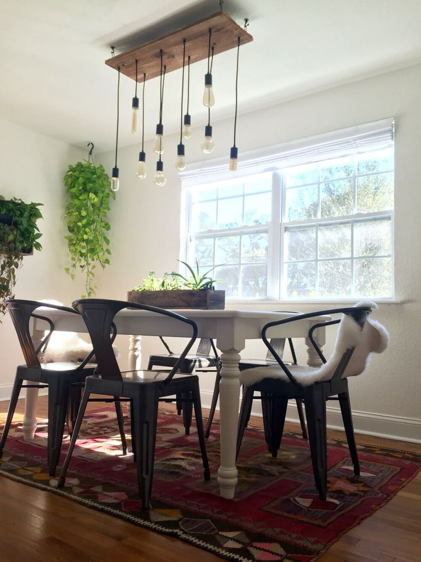 An exciting rustic chandelier for dining room with vintage bulb chandelier, a white table, iron black chairs, small carpet, house plants and big windows.