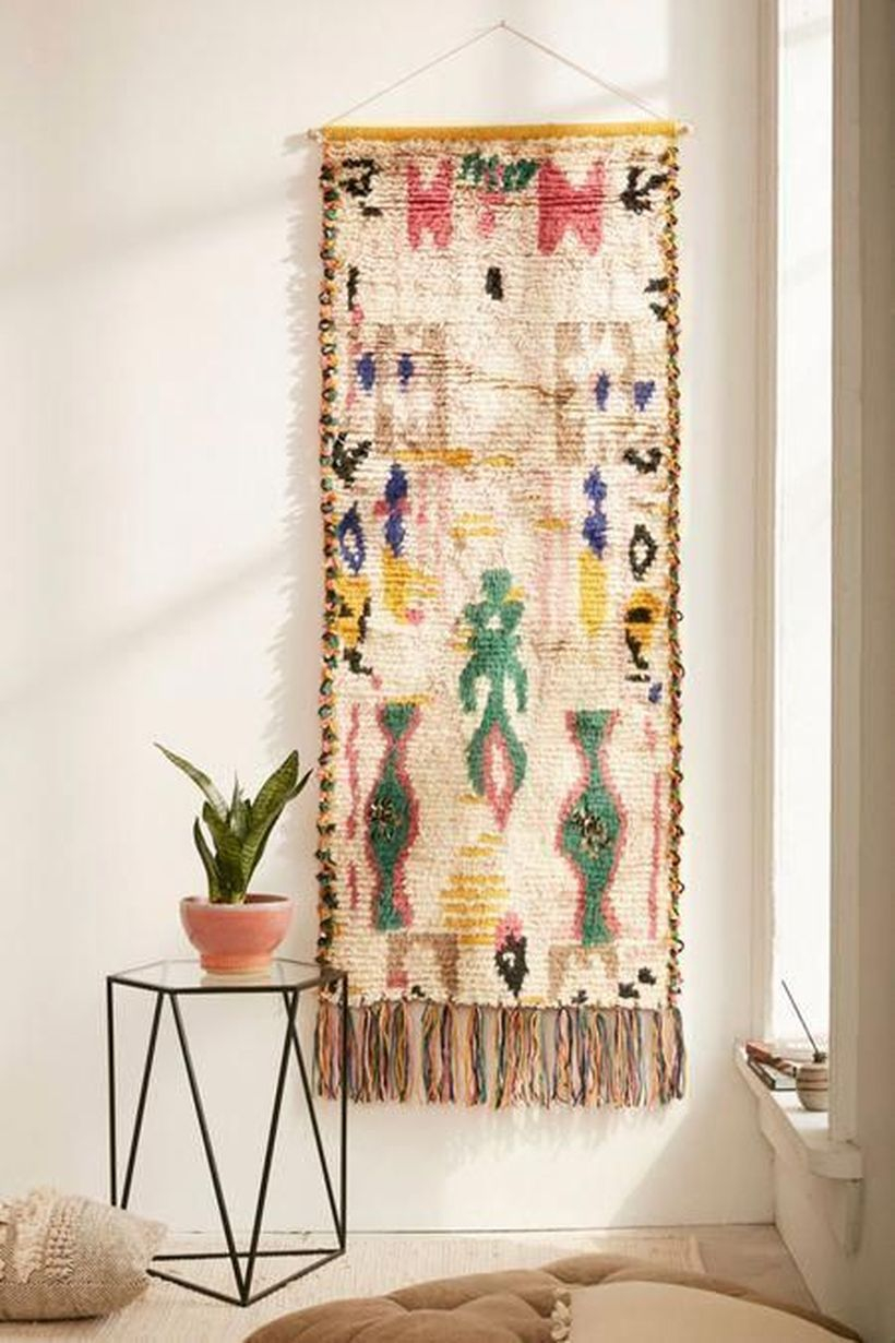 An interesting ornament for bohemian home decorating with bhakti with this tufted shag wall hanging featuring a geo pattern with embellished tufting and long fringed tassels along bottom edge.