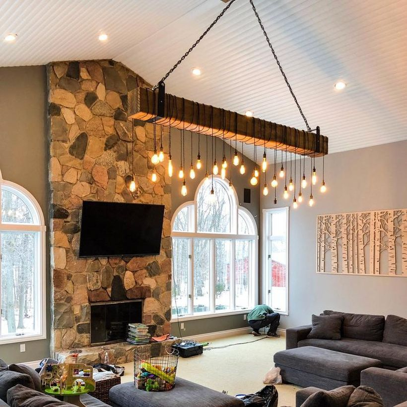 An interesting rustic chandelier for living room with long wooden beam chandelier, grey sofas, stone fireplace, large windows and decoration on the wall.