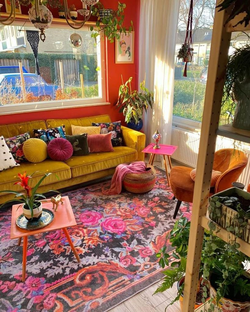 Beautiful boho living room design with floral motifs in red, small square tables, yellow sofas, brown sofas, colorful sofa cushions, rattan baskets, and green plants as a complement