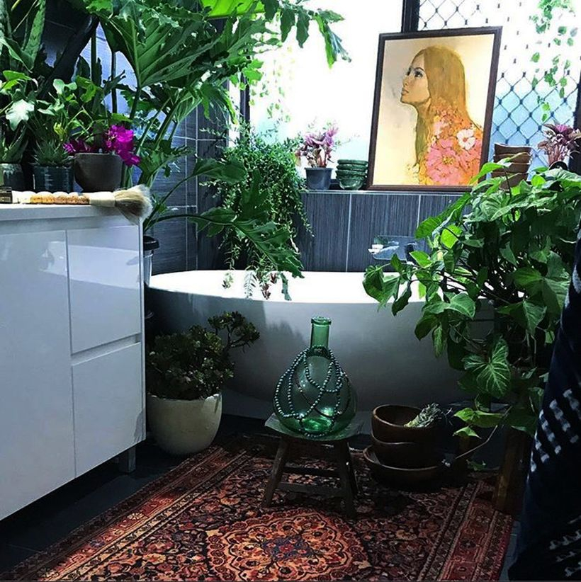Gorgeous boho bathroom decor with square carpet motif, white storage cabinet, painting on the edge of the bathtub and green cover for air conditioning
