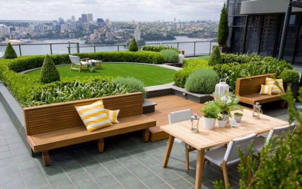 Modern large rooftop projects with wooden seating combined with plants around it to perfect your rooftop garden