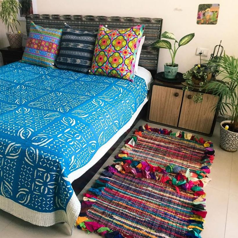 Stunning boho bedroom style blue blanket with white pattern, colorful pillow and colorful striped carpet to look beautiful