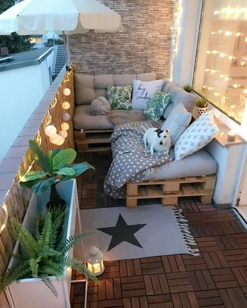 Wooden floor and pallet sofas combined with string lamps for balcony