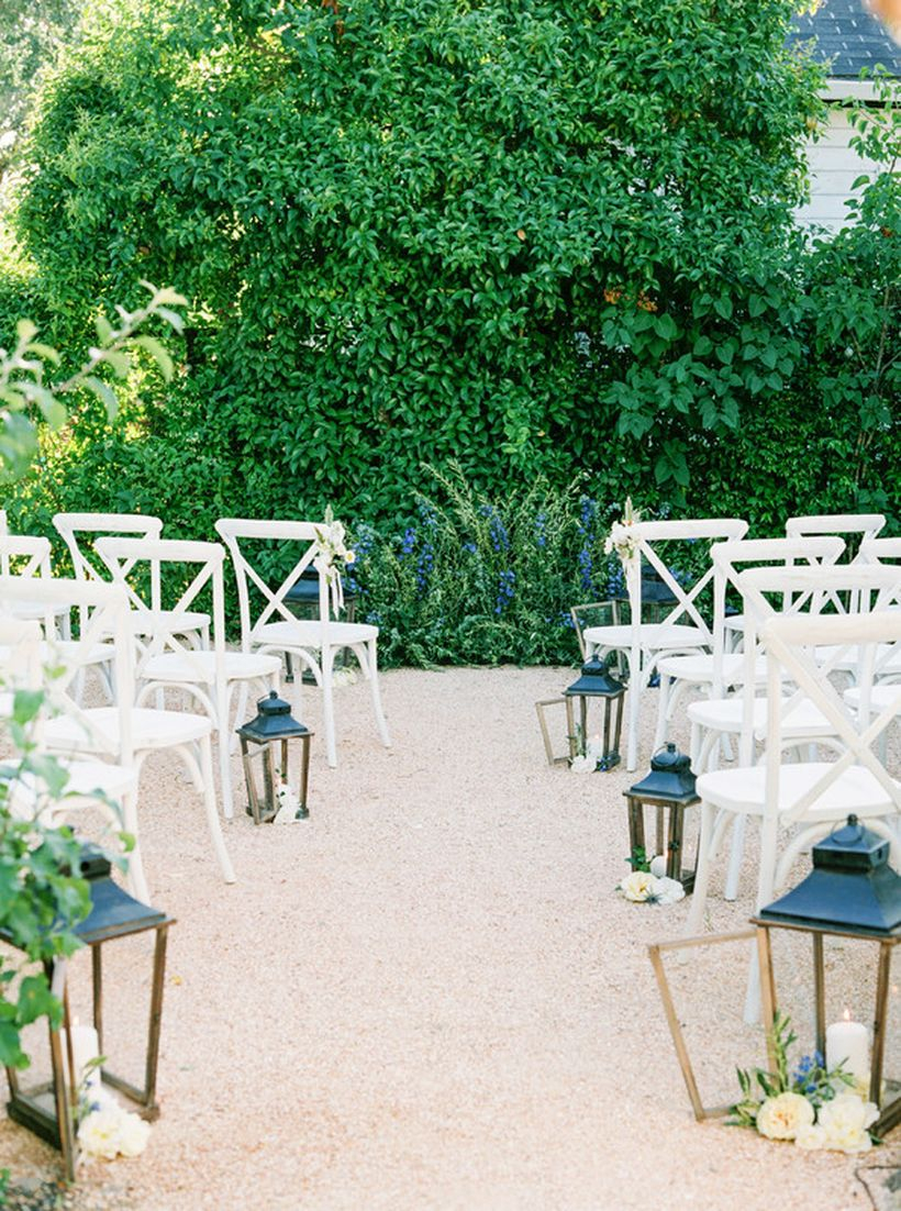 Decorative candle in lanterns and white chair for wedding outdoor