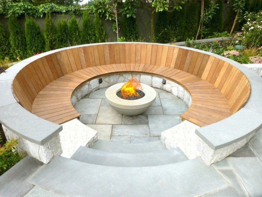 Outdoor curved fire pit with wooden pallet for sitting