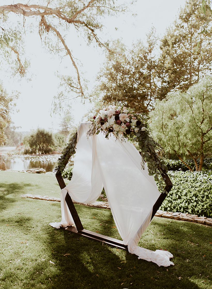 Romantic and moody geometric inspired wedding with backdrop shape hexagon from wooden and add floral to create beautify