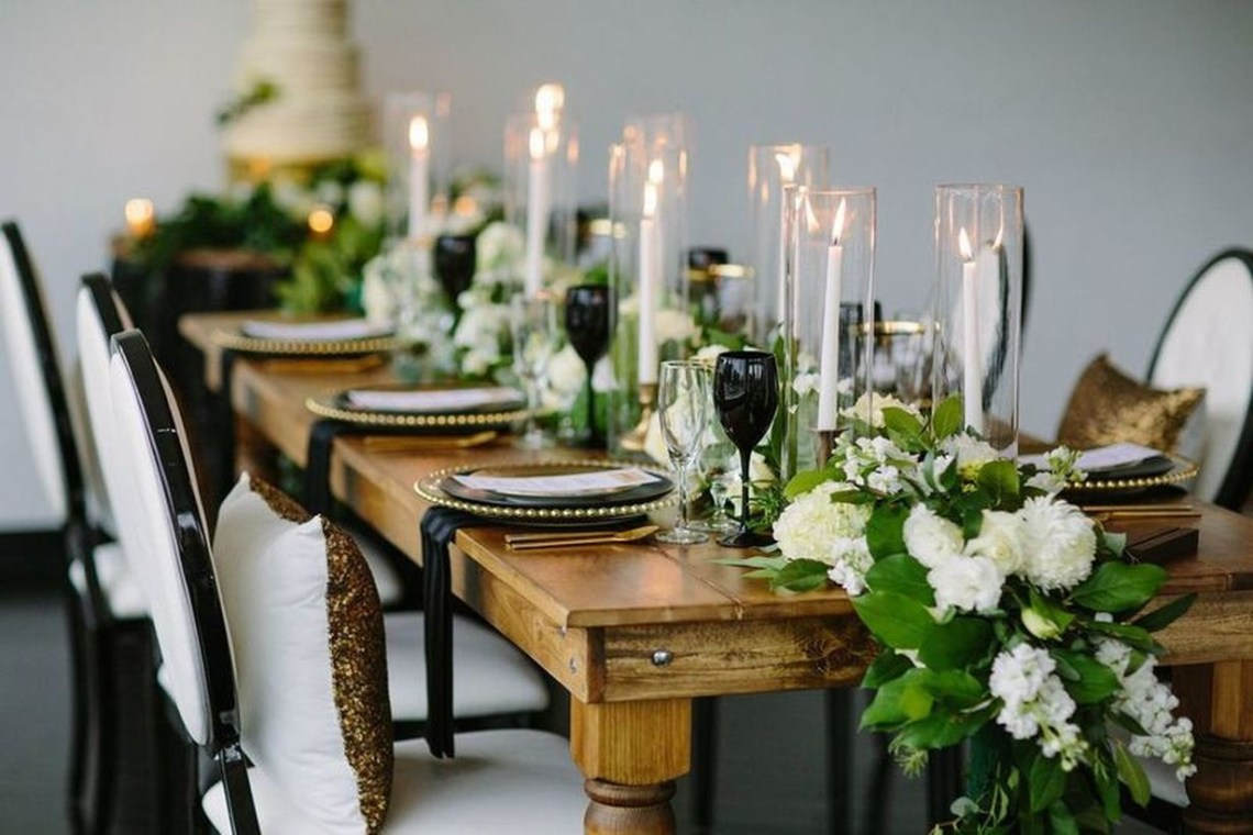 Romantic wedding decoration with monochromatic flowers and taper candles to complete the look