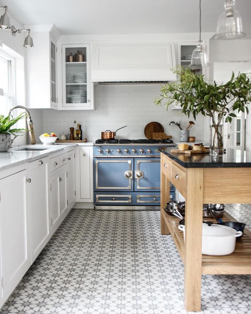 A small sun-patterned kitchen floor on a white floor with a white cabinet and wooden table to look simple