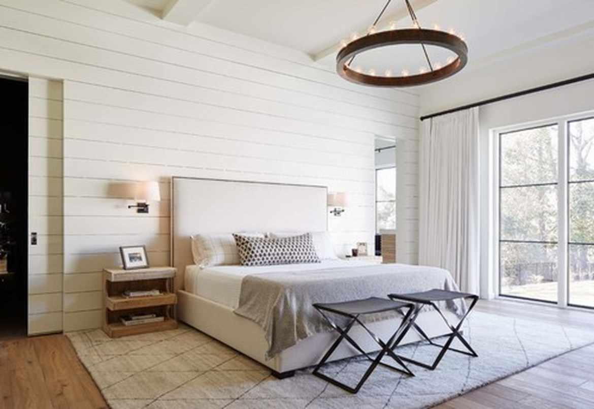 An awesome white bedroom with white bed, wooden chairs, white wooden walls and round wooden candle lamps