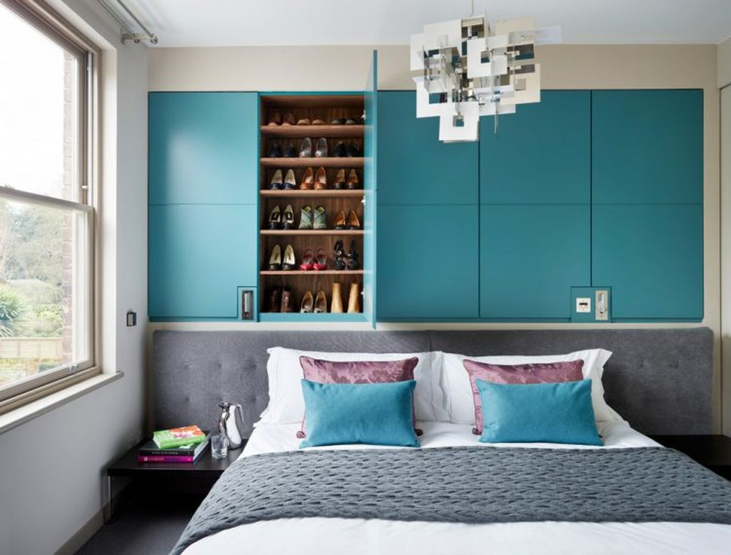 An amazing shoes storage idea for a small bedroom with shelves above the headboard to organize your shoes storage
