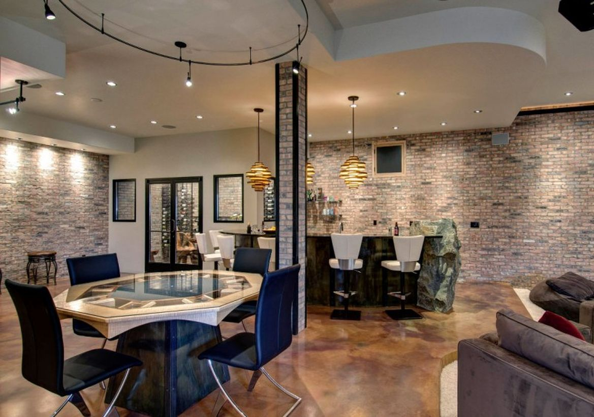 Basement with stone bar, roun white table, black chairs and unique hanging lamps