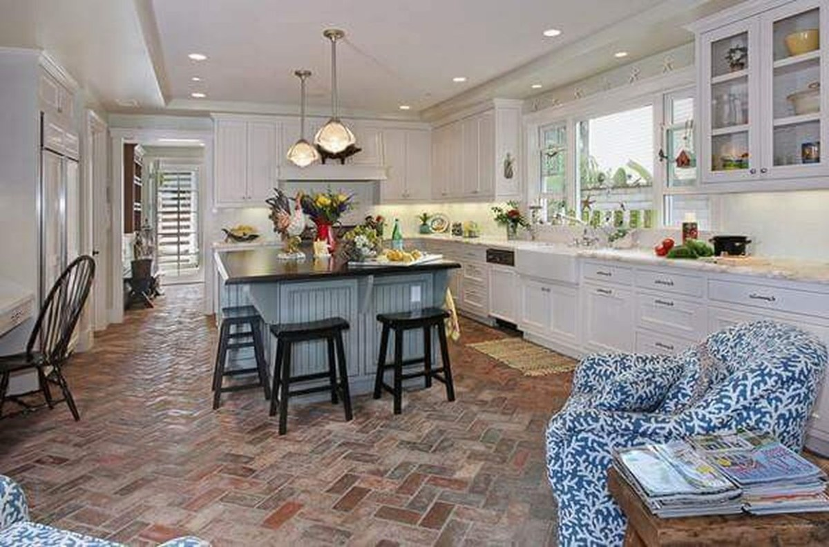 Classic brick kitchen floor with white cabinet, blue island table from wood and modern hanging lamps decoration