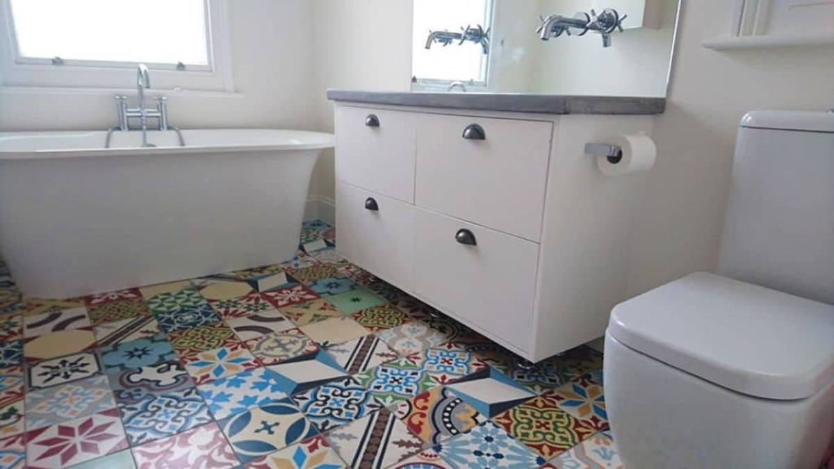 Creative bathroom with white fixtures and colorful patchwork tiles for smart decoration