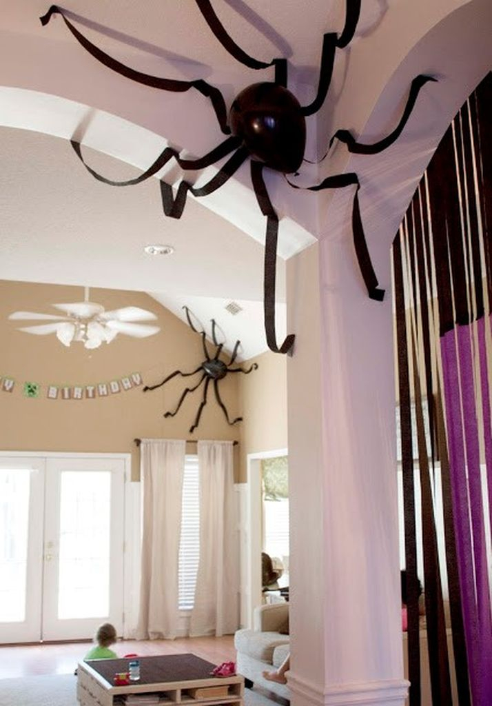 Creative indoor home decoration with black balloons and crepe paper spiders to perfect your halloween decorations