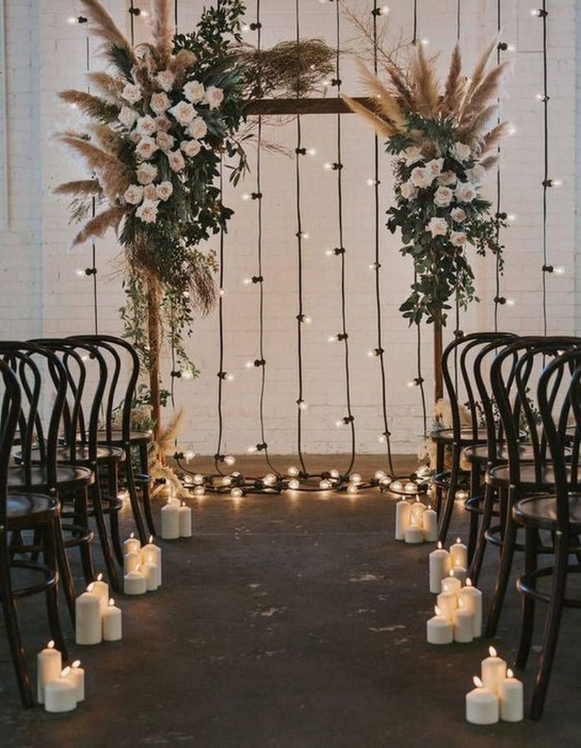 Diy bohemian wedding arch with cendle lights and white flowers decoration