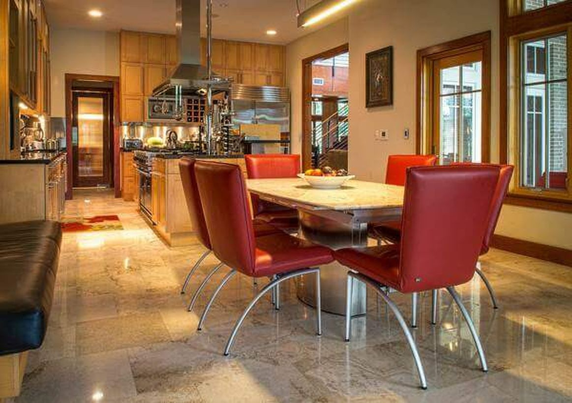 Elegant beige kitchen flooring with modern cabinet, red chairs and square wooden