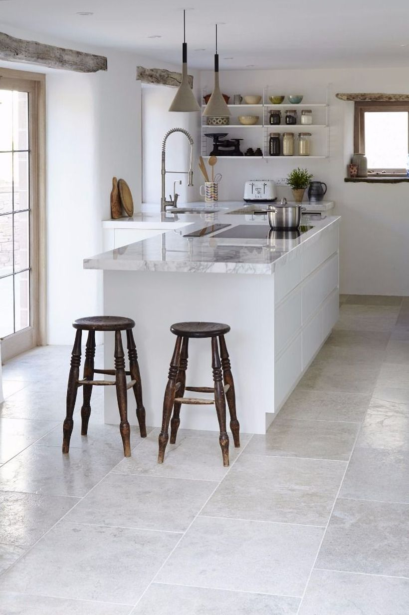 Gray brushed limestone kitchen floor tiles with white island table and small wooden chairs ideas