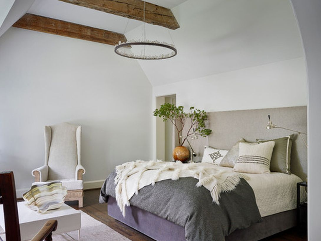 Intresting bedroom with white bed, small square white table and round wooden candle lamp to look unique
