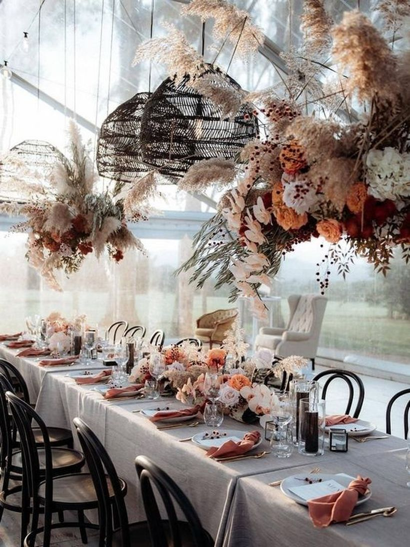 Boho chic table in rust and blush shades with lush florals on the table and over it, wicker lamps, colored napkins and candles
