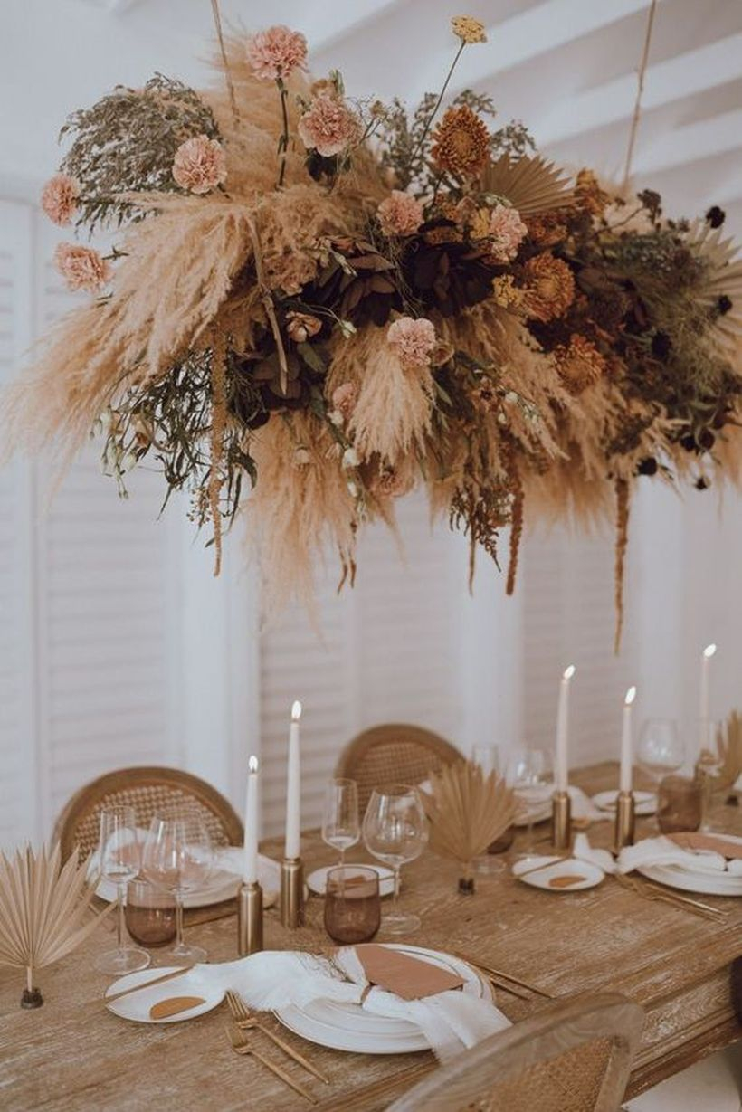 Boho table with black napkins and candles, wicker chargers, geometric touches, dried florals and pampas grass