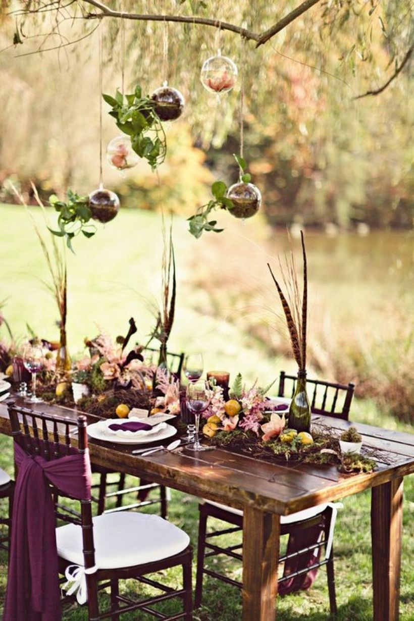 Boho tablescape with a moss and bloom runner, feathers in bottles, colorful textiles and suspended ornaments with petals
