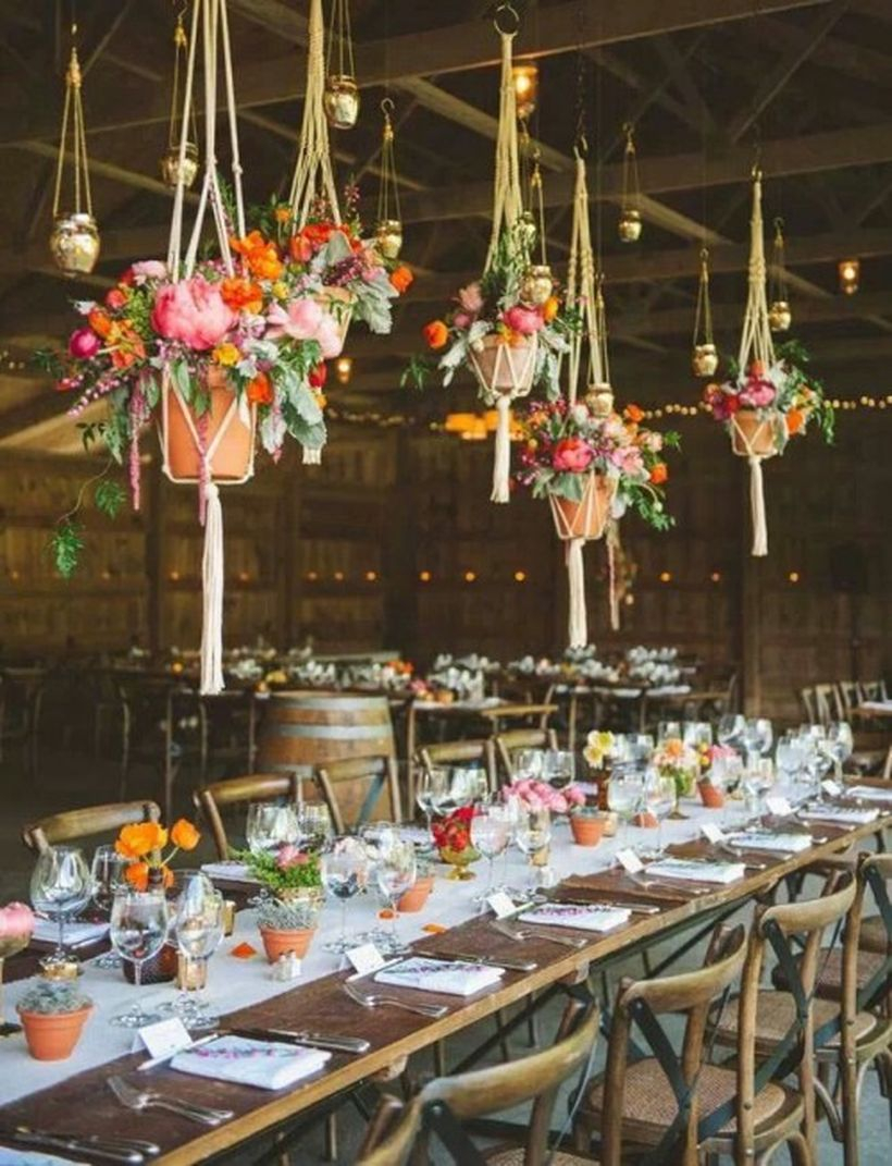 Potted blooms and greenery plus hanging planters with colorful flowers over the table make it bright and boho