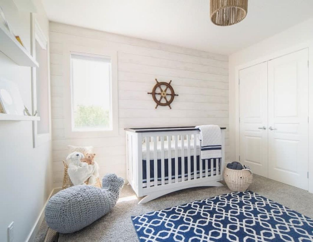 Unique-nursery-for-baby-boys-with-a-sea-theme-white-wooden-pallet-wall-and-big-shark-knit-doll