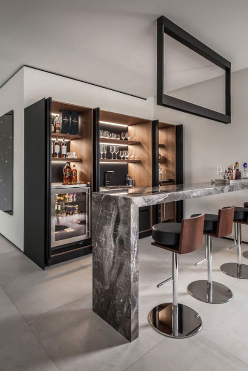 Black coffee bar combined with lights inside, a black and white table and small sofa chairs