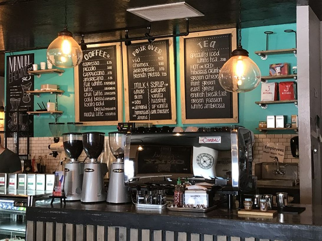 Dark brown wooden coffee bar with chalkboard, green wall and hanging lamps