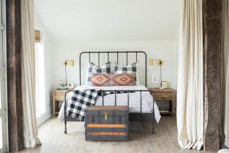 Farmhouse-bedroom-with-wooden-nightstands-a-forged-bed.-1