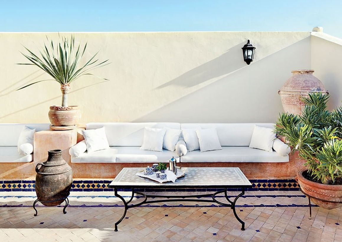 Rustic-seating-rooftop-area-with-a-long-white-sofa-and-classic-coffee-table-plus-plants-to-create-a-cool-atmosphere