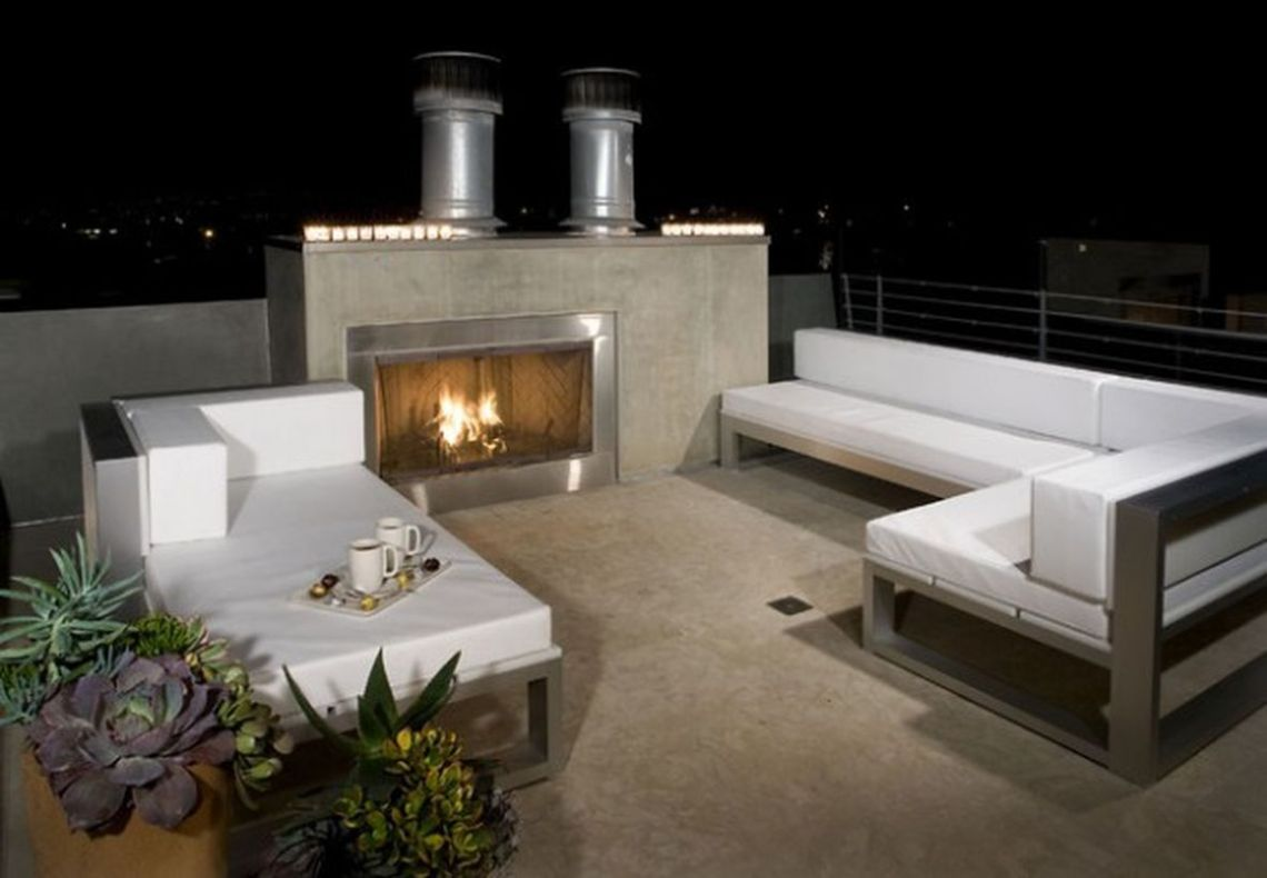 Comfortable-rooftop-design-with-fire-pit-and-white-sofas-to-relax-at-night-and-warm-up