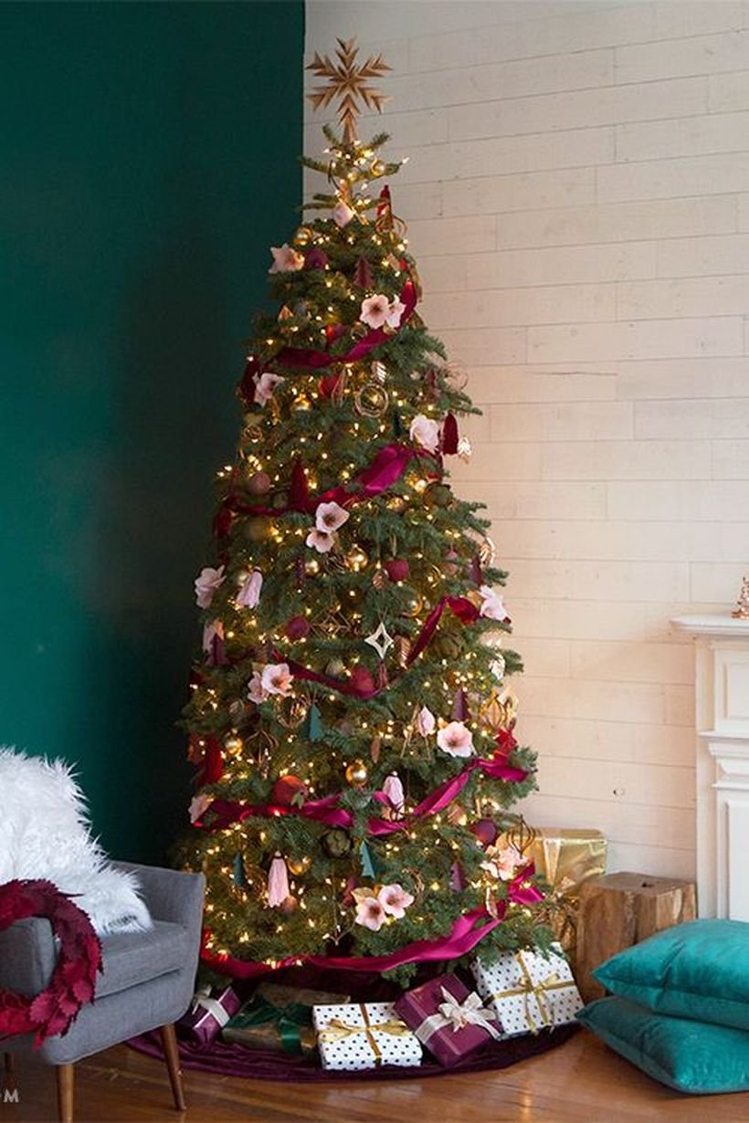 Green-christmas-tree-with-gold-bell-ornament-white-flower-ornament-and-wrapped-in-pink-magenta-fabric-to-decorate-the-tree-to-look-beautiful