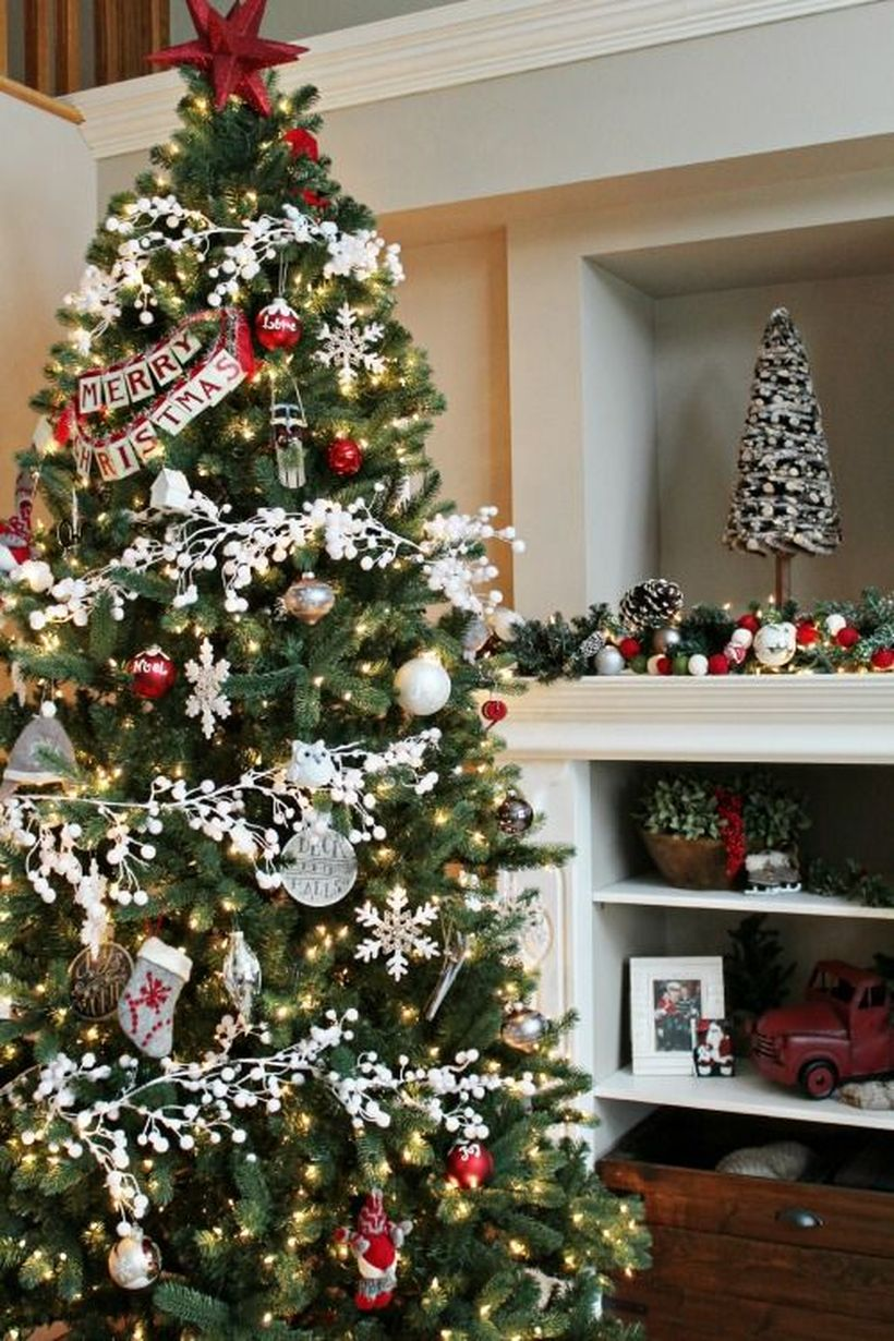 Green-christmas-tree-with-various-ornaments-such-as-bell-ornament-socks-ornament-and-merry-christmas-greeting-from-paper