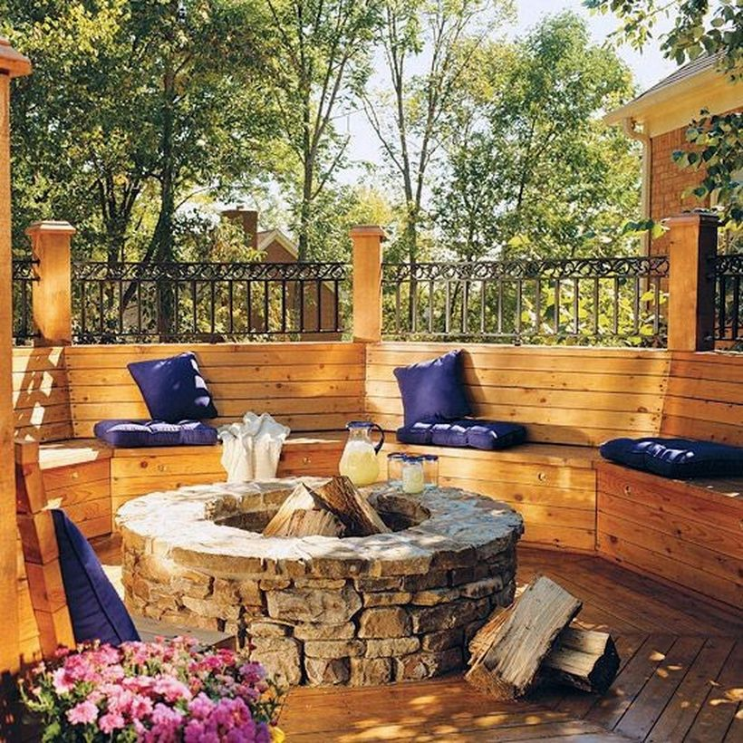Nice-patio-deck-with-natural-stone-fire-pit-and-curved-wooden-bench-with-sofa-cushion-for-comfortable-sitting
