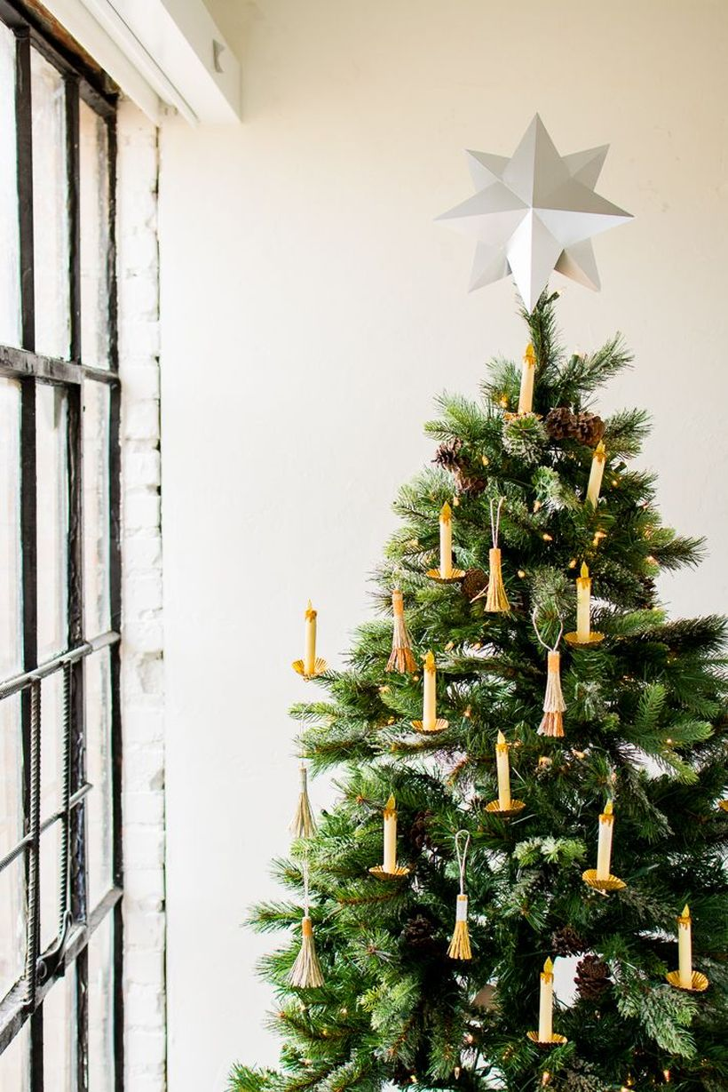 Paper-candle-that-was-hung-on-the-green-christmas-tree-as-an-ornament-that-adorns-the-tree-and-the-top-big-star-for-additional-ornament