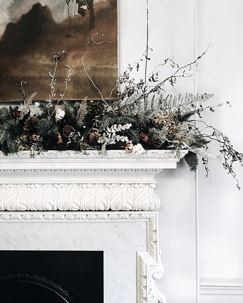 Neutral fireplace with branch and flowers above it