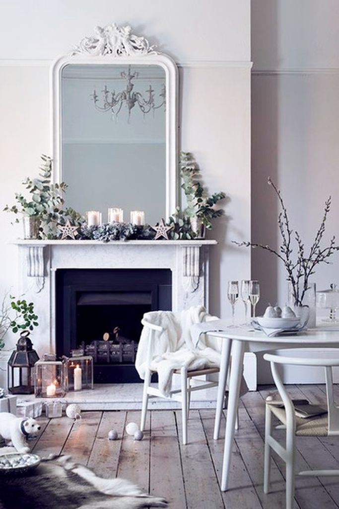 White fireplace wtih plants and big mirror above it