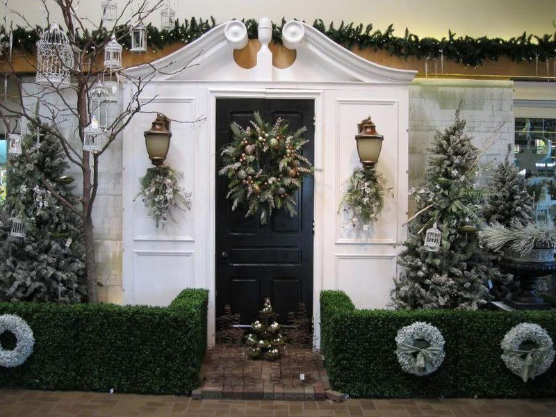 White-and-gold-baubles-and-pine-cones-on-the-front-door-contains-pine-leaves.