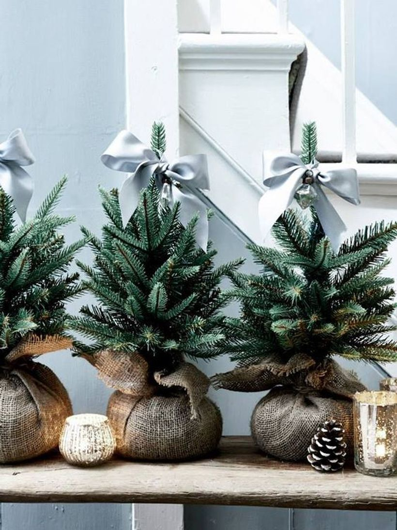08-a-trio-of-little-christmas-trees-wrapped-in-burlap-and-topped-with-grey-ribbon-bows-for-a-cute-look