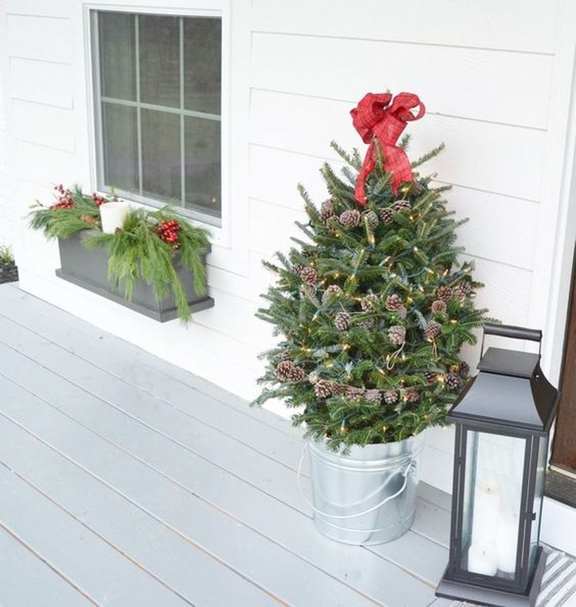 22-a-small-holiday-tree-decorated-with-lights-pinecones-and-a-red-bow-on-top-in-a-galvanized-bucket-for-a-porch