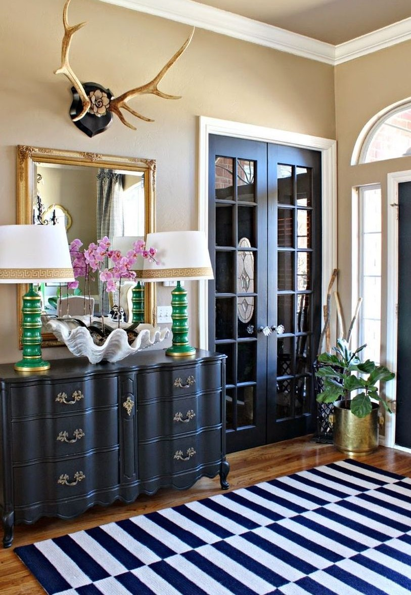 3bold-and-eclectic-entryway-with-a-gold-framed-mirror-and-antler-decor-above-it-2