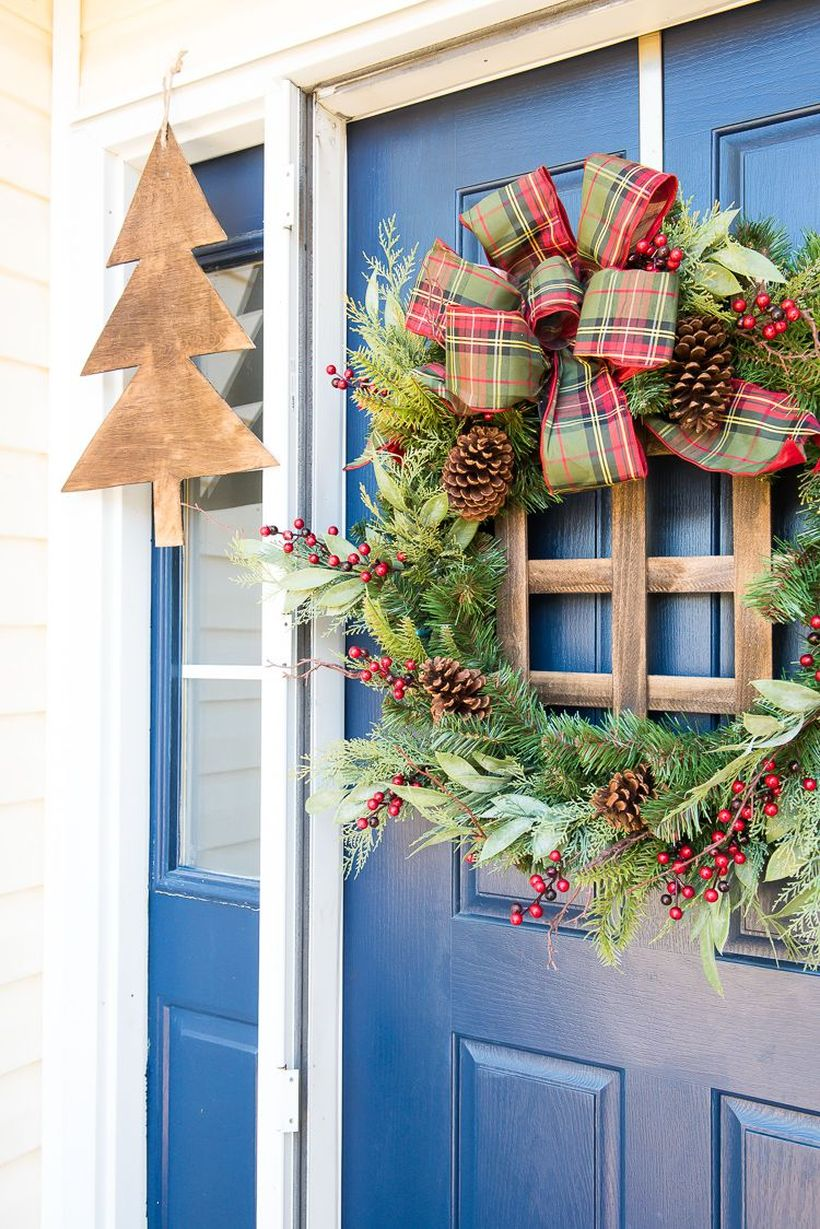 Welcoming-christmas-front-door-with-a-plaid-wreath.-this-blogger-simply-attached-wood-crossbars-to-a-store-bought-wreath-for-a-completely-different-look.