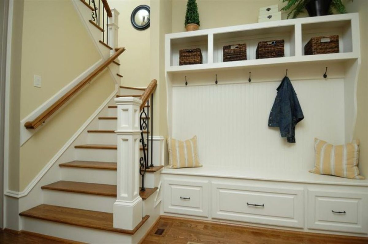 White-wood-entryway-bench-seat-with-coat-rack-and-clothing-hooks-beside-stairs-with-drawer-pillow-and-small-rattan-storage-ideas-783x520
