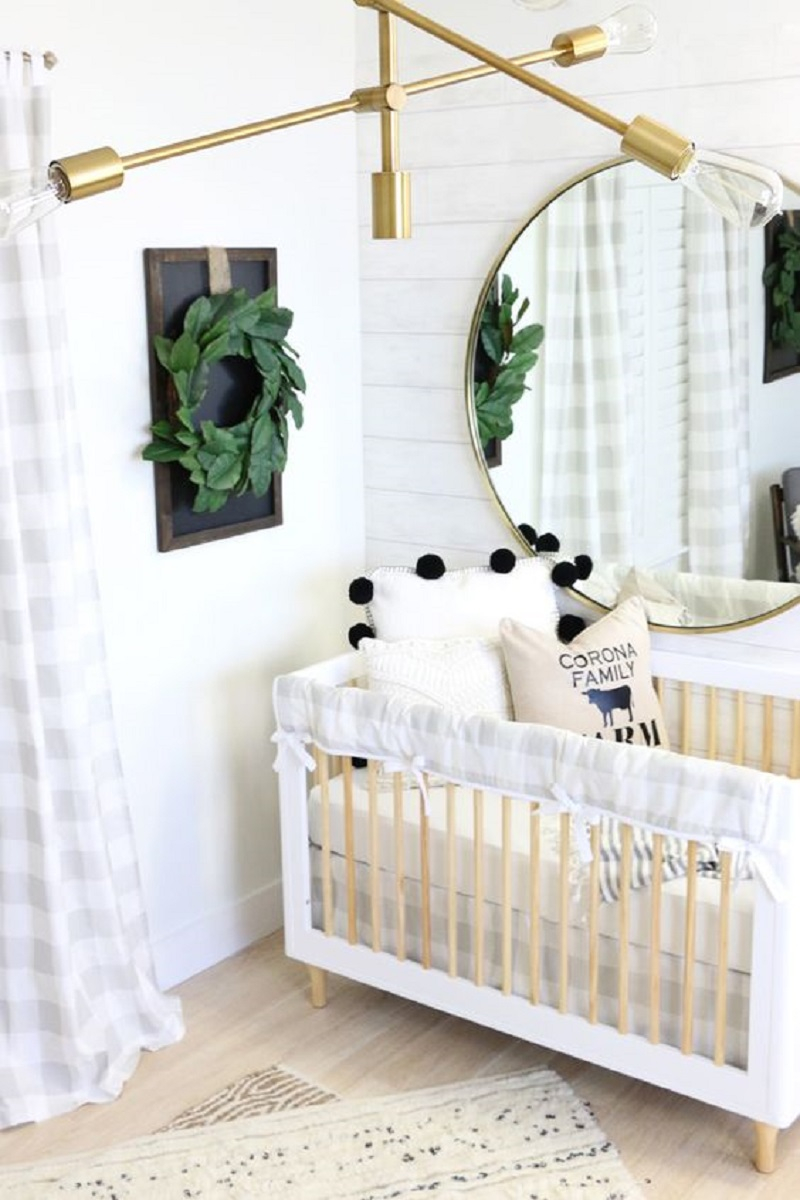 A-modern-farmhouse-nursery-with-white-plank-walls-a-neutral-wooden-crib-a-gold-chandelier-and-a-greenery-wreath