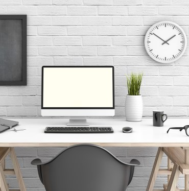 Table with pc in front of a white wall