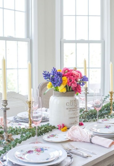 1 a-spring-tablescape-with-bright-porcelain-a-colorful-floral-centerpiece-a-eucalyptus-runner-candles-and-pink-napkins